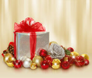 Christmas gift and balls. Christmas scene with silver gift and gold and red balls on golden background Royalty Free Stock Photography