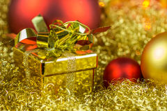 Christmas gift and balls on golden background Stock Photos