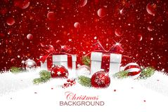 Christmas gift with balls. In snow on a red glittering background Royalty Free Stock Image