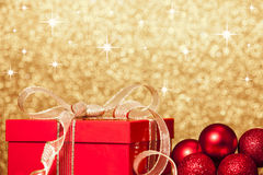 Christmas Gift and Baubles on Defocused Lights Background Stock Images
