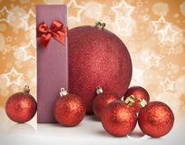 Christmas gift and baubles on golden background Royalty Free Stock Images