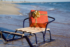 Christmas gift on the beach. In a sleigh Royalty Free Stock Photos