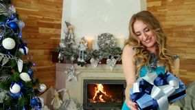 Christmas gift, beautiful girl enjoys gifts in hands Christmas miracle, portrait of female, gives a festive wrapped stock video