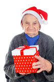 Christmas gift for a beautiful grandmother. Picture of an elderly woman holding a Christmas gift stock photography