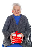 Christmas gift for a beautiful grandmother. Picture of an elderly woman holding a Christmas gift stock photos