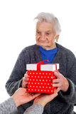 Christmas gift for a beautiful grandmother. Picture of an elderly woman receiving a Christmas gift royalty free stock photos