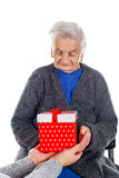 Christmas gift for a beautiful grandmother. Picture of an elderly woman receiving a Christmas gift stock image