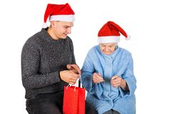 Christmas gift for a beautiful grandmother. Picture of an old lady receiving Christmas gifts from her grandson royalty free stock photography