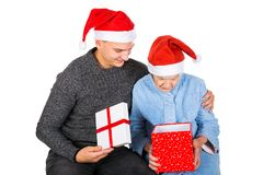 Christmas gift for a beautiful grandmother. Picture of an old lady receiving Christmas gifts from her grandson royalty free stock images