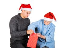 Christmas gift for a beautiful grandmother. Picture of an old lady receiving Christmas gifts from her grandson stock photos