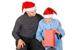 Christmas gift for a beautiful grandmother. Picture of an old lady receiving Christmas gifts from her grandson stock photo