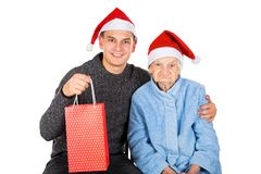 Christmas gift for a beautiful grandmother. Picture of an old lady receiving Christmas gifts from her grandson royalty free stock photo