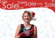 Christmas gift. Beautiful womanin santa hat. Holiday sale stock photography