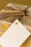 Christmas gift with blank tag gold ribbon Royalty Free Stock Photos