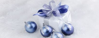 Christmas gift and blue Christmas balls on a festive white back. Ground .photo with copy space Stock Images