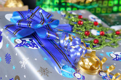 Christmas gift with a blue ribbon. Wrapped Christmas gift with a blue ribbon with golden stripes and a small Christmas tree ornament with red balls on the side Royalty Free Stock Image