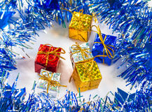 Christmas gift in blue wreath with festive decor. Royalty Free Stock Photography