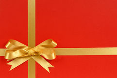 Christmas gift border frame with gold ribbon and bow. Red background, copy space stock photos