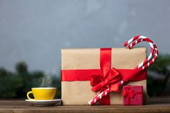 Christmas gift with bowknot and cup of tea. On grey background royalty free stock photo
