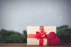 Christmas gift with bowknot and heart shape toy. On grey background royalty free stock image