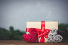 Christmas gift with bowknot and heart shape toys. On grey background royalty free stock photography