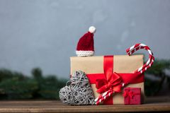Christmas gift with bowknot and lollipop with candy. On grey background royalty free stock photography