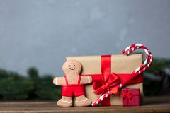 Christmas gift with bowknot and lollipop with gingerbread. On grey background stock images