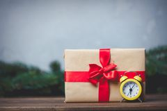 Christmas gift with bowknot and retro alarm clock. On grey background royalty free stock photos