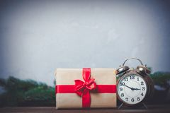 Christmas gift with bowknot and retro alarm clock. On grey background royalty free stock photo