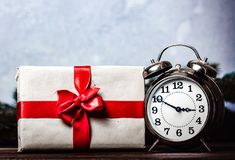Christmas gift with bowknot and retro alarm clock. On grey background stock photography