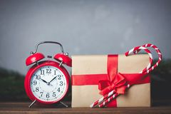 Christmas gift with bowknot and retro alarm clock. With lollipop on grey background stock photography