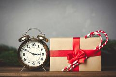 Christmas gift with bowknot and retro alarm clock. With lollipop on grey background royalty free stock photo