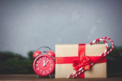 Christmas gift with bowknot and retro alarm clock. With lollipop on grey background stock photo