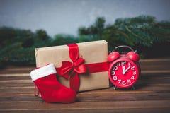 Christmas gift with bowknot and retro alarm clock. Near Santa Claus sock on grey background stock photos