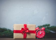 Christmas gift with bowknot and retro alarm clock. On grey background royalty free stock images