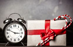 Christmas gift with bowknot and retro alarm clock. With lollipop on grey background royalty free stock image