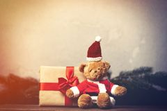 Christmas gift with bowknot and teddy bear toy. On grey background royalty free stock images