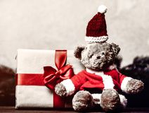 Christmas gift with bowknot and teddy bear toy. On grey background stock photography