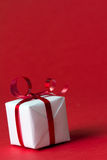 Christmas gift box. White gift box with red ribbon isolated on red color background Royalty Free Stock Photography