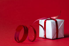 Christmas gift box. White gift box with red ribbon  on red color background Stock Images