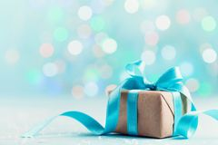 Christmas gift box against blue bokeh background. Holiday greeting card.