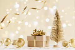 Christmas gift box against golden bokeh background. Holiday greeting card. royalty free stock photo
