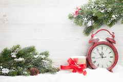 Christmas gift box, alarm clock and fir tree branch Stock Photo