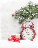 Christmas gift box, alarm clock and fir tree branch Royalty Free Stock Images