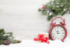 Christmas gift box, alarm clock and fir tree. Branch covered by snow in front of wooden wall. View with copy space Royalty Free Stock Photo