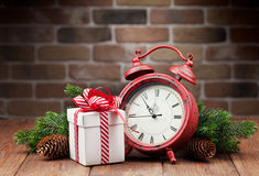 Christmas gift box, alarm clock and tree branch Royalty Free Stock Photos
