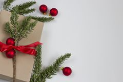 Christmas Gift Box Background with Ornaments. A Christmas gift box with a red bow with rosemary greens and ornaments. Frame left justified stock image