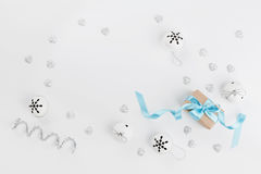 Christmas gift box with blue ribbon and jingle bell on white background from above. Holiday greeting card. Mockup. Flat lay frame. Stock Photo