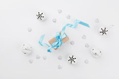 Christmas gift box with blue ribbon and jingle bell on white table from above. Holiday greeting card. Mockup. Flat lay composition Royalty Free Stock Photo