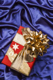 Christmas gift box on blue satin background. Gift box with gold ribbon. Vertical orientation Stock Photography